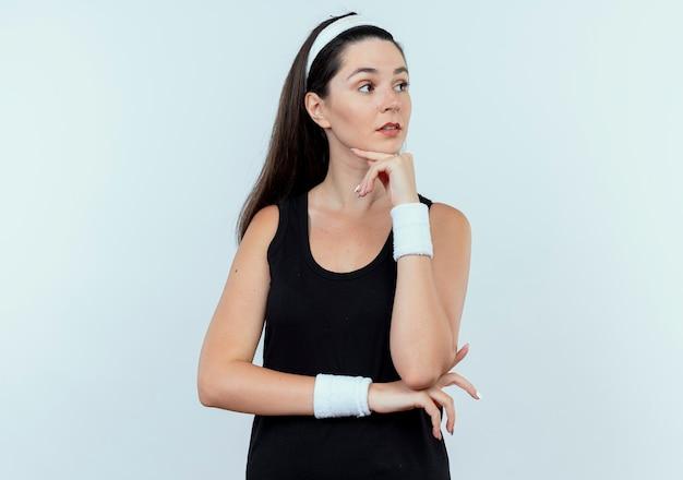 Jonge fitness vrouw in hoofdband opzij kijken met hand op kin denken staande op witte achtergrond
