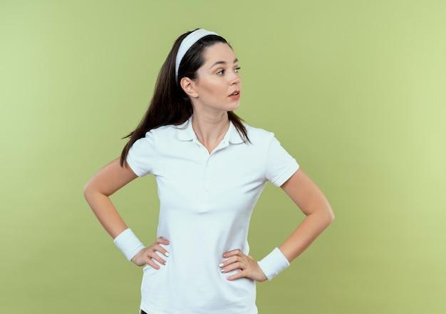 Jonge fitness vrouw in hoofdband opzij kijken met zelfverzekerde uitdrukking met armen op heup staande over lichte achtergrond