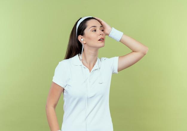 Jonge fitness vrouw in hoofdband opzij kijken met zelfverzekerde uitdrukking staande over lichte muur