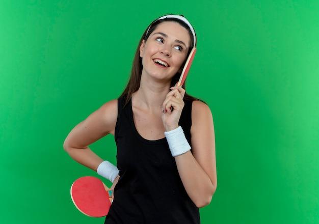 Jonge fitness vrouw in hoofdband rackets voor tafeltennistafel opzij kijken glimlachend met blij gezicht staande over blauwe muur