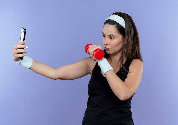 Jonge fitness vrouw in hoofdband selfie met behulp van haar smartphone weergegeven: halter had op zoek zelfverzekerd staande op blauwe achtergrond