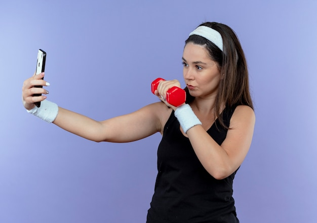 Jonge fitness vrouw in hoofdband selfie met behulp van haar smartphone weergegeven: halter in had op zoek zelfverzekerd staan over blauwe muur