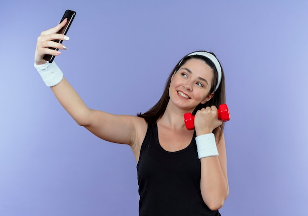 Jonge fitness vrouw in hoofdband selfie met behulp van smartphone houden halter glimlachend met blij gezicht staande over blauwe achtergrond