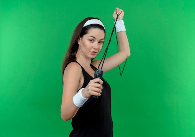 Jonge fitness vrouw in hoofdband springtouw met zelfverzekerde uitdrukking staande over groene muur te houden