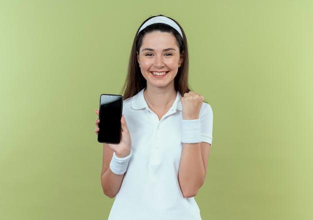 Jonge fitness vrouw in hoofdband tonen smartphone gebalde vuist happyand opgewonden staande over lichte muur