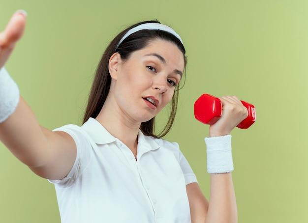 Jonge fitness vrouw in hoofdband uit te werken met halter camera kijken met zelfverzekerde uitdrukking staande over lichte achtergrond
