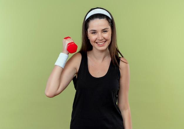 Jonge fitness vrouw in hoofdband uit te werken met halter lachend met blij gezicht staande over lichte achtergrond