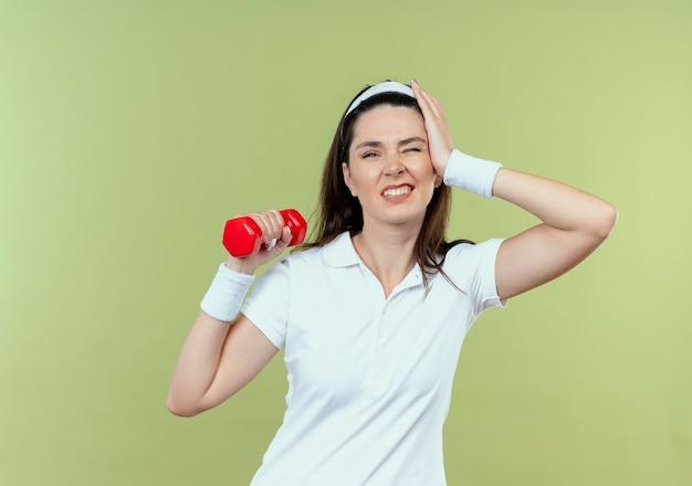 Jonge fitness vrouw in hoofdband uit te werken met halter op zoek verward staande over lichte muur
