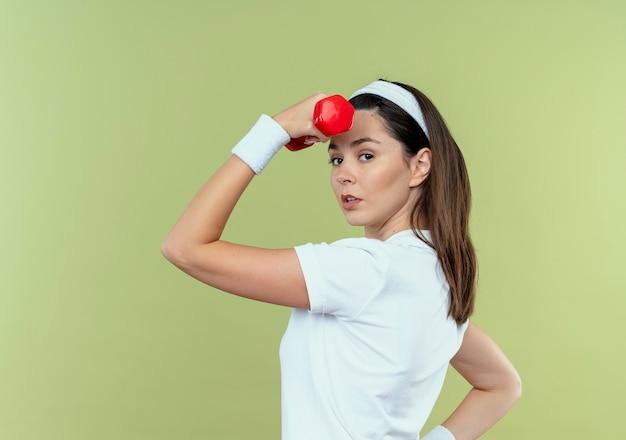 Jonge fitness vrouw in hoofdband uit te werken met halter op zoek zelfverzekerd staande over lichte achtergrond