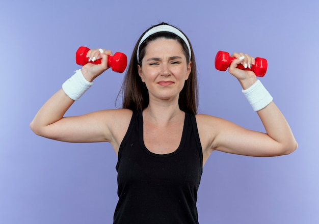 Jonge fitness vrouw in hoofdband uit te werken met halters gespannen en zelfverzekerd permanent over blauwe achtergrond