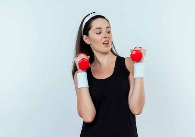 Jonge fitness vrouw in hoofdband uit te werken met halters op zoek gespannen en zelfverzekerd staande op witte achtergrond