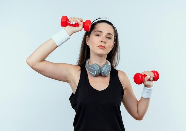 Jonge fitness vrouw in hoofdband uit te werken met halters op zoek moe staande op witte achtergrond