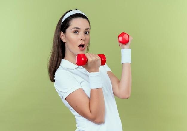 Jonge fitness vrouw in hoofdband uit te werken met halters op zoek verrast staande over lichte achtergrond