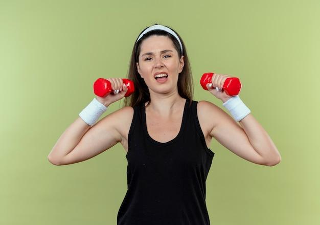 Jonge fitness vrouw in hoofdband uit te werken met halters op zoek verward staande over lichte muur