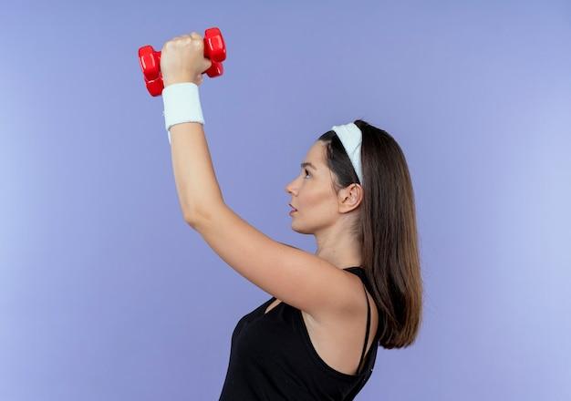 Jonge fitness vrouw in hoofdband uit te werken met halters op zoek zelfverzekerd staande over blauwe achtergrond