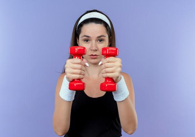 Jonge fitness vrouw in hoofdband uit te werken met halters op zoek zelfverzekerd staande over blauwe muur