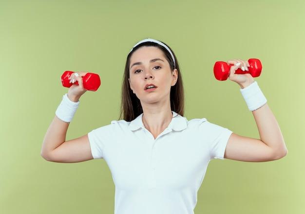 Jonge fitness vrouw in hoofdband uit te werken met halters op zoek zelfverzekerd staande over lichte muur