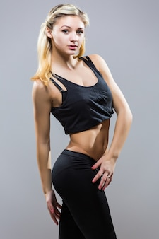 Jonge fitness vrouw in sport stijl staande tegen een witte achtergrond. geïsoleerd