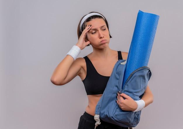 Jonge fitness vrouw in sportkleding bedrijf rugzak met yoga mat opzij kijken verward en moe waait wangen staande over witte muur