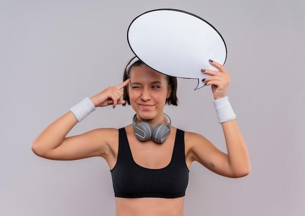 Jonge fitness vrouw in sportkleding die met hoofdband het lege teken van de toespraakbel houdt die haar tempel richt die zich over witte muur probeert te concentreren