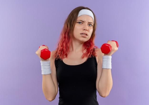 Jonge fitness vrouw in sportkleding doet oefeningen met halters met geïrriteerde uitdrukking staande over paarse muur