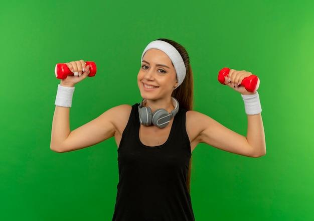 Jonge fitness vrouw in sportkleding doet oefeningen met twee halters glimlachend vrolijk blij en opgewonden staande over groene muur