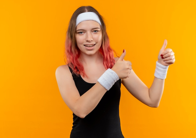 Jonge fitness vrouw in sportkleding glimlachend vrolijk opdagen duimen met beide handen permanent over oranje muur