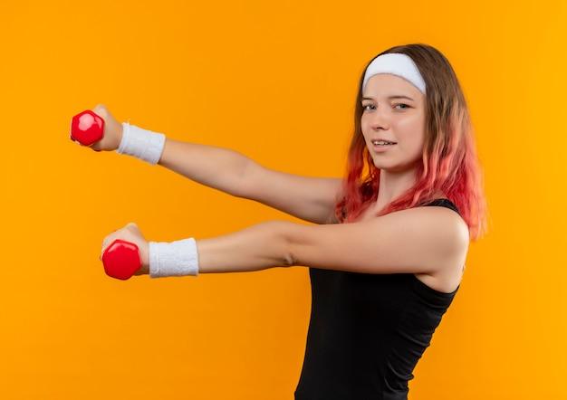Jonge fitness vrouw in sportkleding met behulp van halters doen oefeningen op zoek zelfverzekerd glimlachend staande over oranje muur