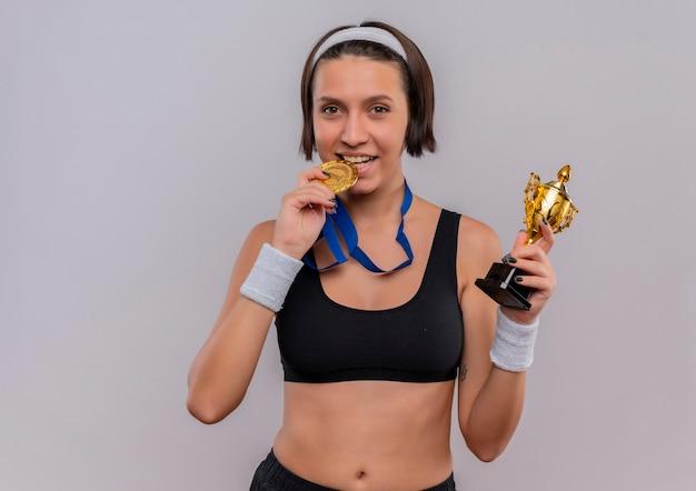 Jonge fitness vrouw in sportkleding met gouden medaille om haar nek die haar trofee blij en positief vasthoudt terwijl ze haar medaille bijtend over witte muur staande houdt
