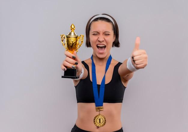 Jonge fitness vrouw in sportkleding met gouden medaille om haar nek houdt haar trofee blij en opgewonden verheugd over haar succes met duimen omhoog staande over witte muur