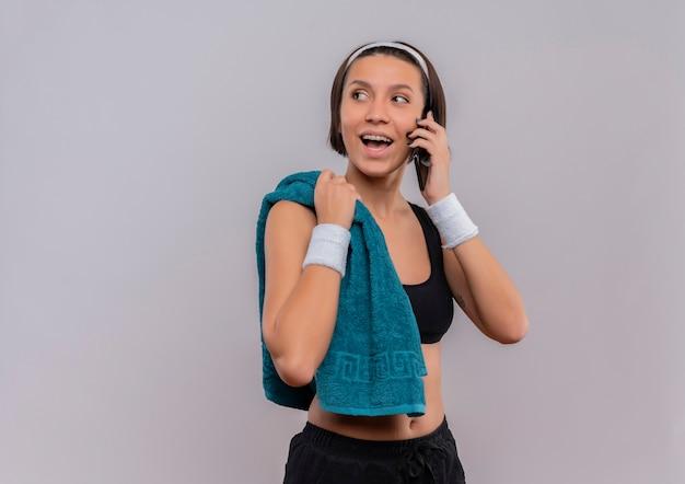 Jonge fitness vrouw in sportkleding met handdoek op schouder vrolijk lachend tijdens het praten op mobiele telefoon staande over witte muur