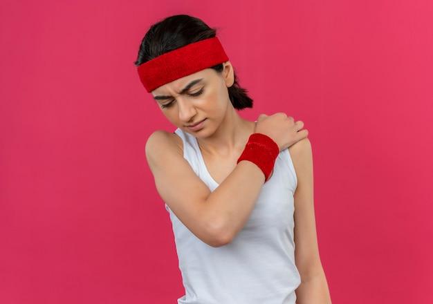 Jonge fitness vrouw in sportkleding met hoofdband aanraken van haar schouder op zoek onwel gevoel pijn staande over roze muur