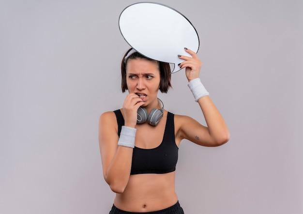 Jonge fitness vrouw in sportkleding met hoofdband bedrijf leeg tekstballon teken opzij kijken verbaasd staande over witte muur