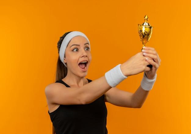 Jonge fitness vrouw in sportkleding met hoofdband bedrijf trofee blij en opgewonden staande over oranje muur