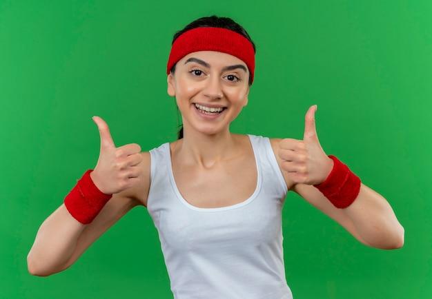 Jonge fitness vrouw in sportkleding met hoofdband blij en positief glimlachend vrolijk tonen duimen omhoog staande over groene muur