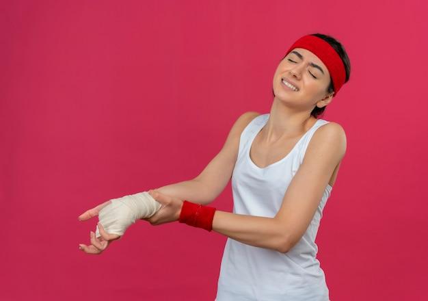 Jonge fitness vrouw in sportkleding met hoofdband die onwel kijkt wat betreft haar verbonden pols met pijn die zich over roze muur bevindt