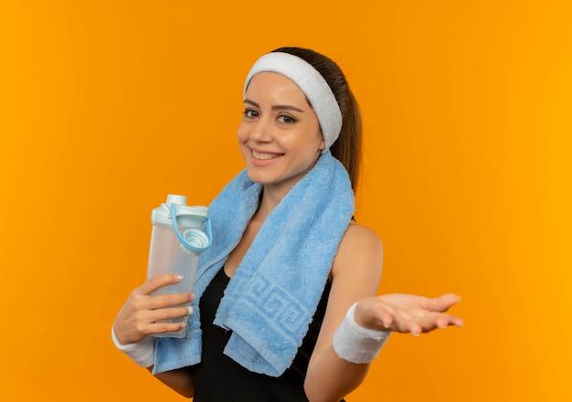 Jonge fitness vrouw in sportkleding met hoofdband en handdoek op haar nek met fles water glimlachend vrolijk staande over oranje muur