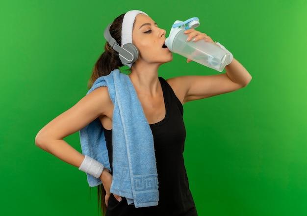 Jonge fitness vrouw in sportkleding met hoofdband en handdoek op haar schouder drinkwater na training staande over groene muur