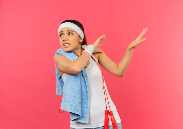 Jonge fitness vrouw in sportkleding met hoofdband en handdoek op haar schouder opzij kijken met walging expressie