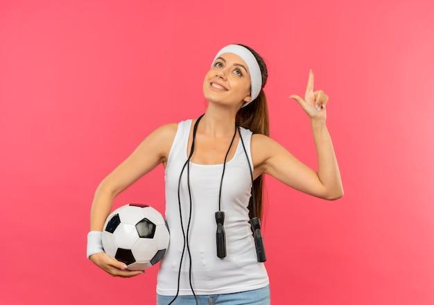Jonge fitness vrouw in sportkleding met hoofdband en springtouw om haar nek met voetbal