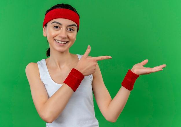 Jonge fitness vrouw in sportkleding met hoofdband glimlachend zelfverzekerd wijzend met wijsvinger naar de zijkant presenteren met arm van haar hand staande over groene muur