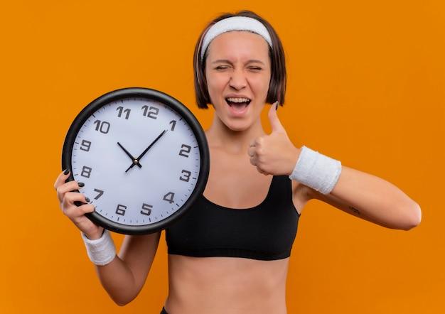 Jonge fitness vrouw in sportkleding met hoofdband houden muurklok blij en opgewonden duimen opdagen staande over oranje muur