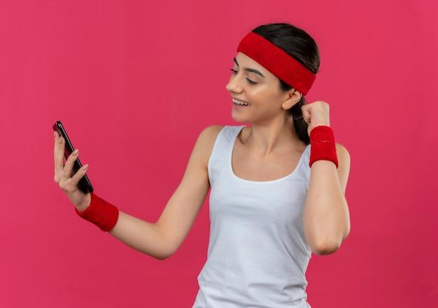 Jonge fitness vrouw in sportkleding met hoofdband houden op het scherm van haar smartphone glimlachend gebalde vuist staande over roze muur