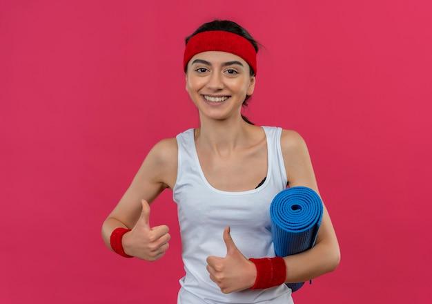 Jonge fitness vrouw in sportkleding met hoofdband houden yoga mat duimen opdagen glimlachend vrolijk staande over roze muur