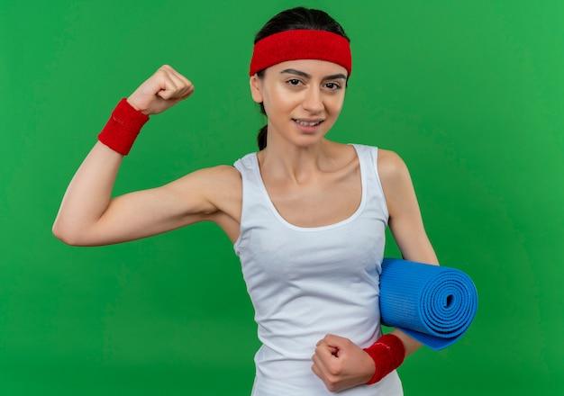 Jonge fitness vrouw in sportkleding met hoofdband houden yoga mat op zoek zelfverzekerd verhogen vuist, winnaar concept staande over groene muur