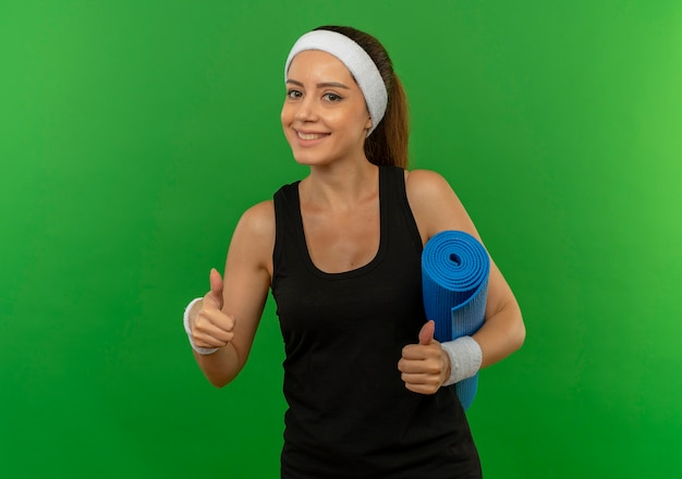 Jonge fitness vrouw in sportkleding met hoofdband houden yogamat duimen opdagen glimlachend zelfverzekerd staande over groene muur