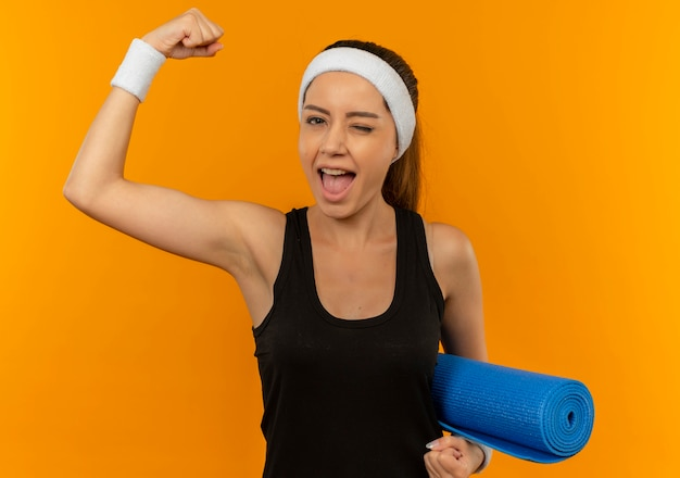 Jonge fitness vrouw in sportkleding met hoofdband houden yogamat opheffen vuist blij en opgewonden staande over oranje muur