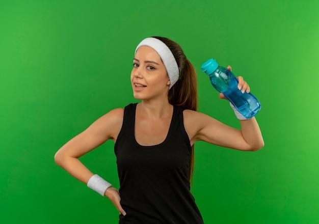 Jonge fitness vrouw in sportkleding met hoofdband met fles water op zoek naar vertrouwen staande over groene muur