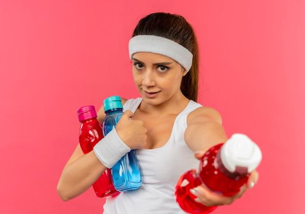Jonge fitness vrouw in sportkleding met hoofdband met flessen water die een van hen aanbiedt die zich over roze muur bevinden