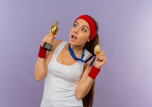 Jonge fitness vrouw in sportkleding met hoofdband met gouden medaille om haar nek en houdt haar trofee op zoek verrast